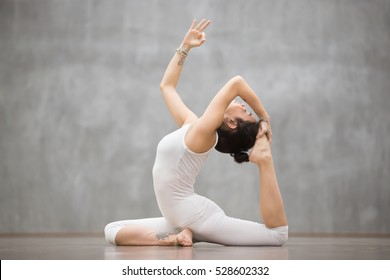 Side view portrait of attractive young woman with beautiful tattoo working out in fitness club or at home, doing yoga or pilates exercise. One Legged King Pigeon pose, Eka Pada Rajakapotasana
