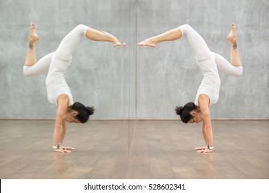 Side view portrait of attractive young woman working out in front of mirror in fitness club, doing yoga or pilates exercise. Handstand, Adho Mukha Vrksasana, Downward facing Tree Pose. Full length