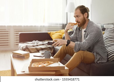 Side view portrait of bearded man eating pizza while watching TV at home in bachelors pad, copy space