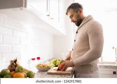 Side view portrait of bearded mature man cooking dinner in kitchen lit by sunlight, copy space