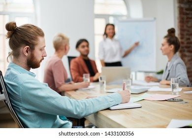 Side view portrait of bearded young man taking notes during business meeting in conference room, copy space