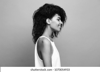 Side view portrait of beautiful attractive African American woman over yellow studio background. Copy Space and duotone.