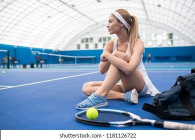 Side view portrait of beautiful blonde woman sitting on floor in indoor tennis court takjing break from practice, copy space