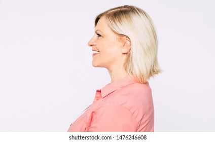 Side view portrait of beautiful blonde smiling senior woman