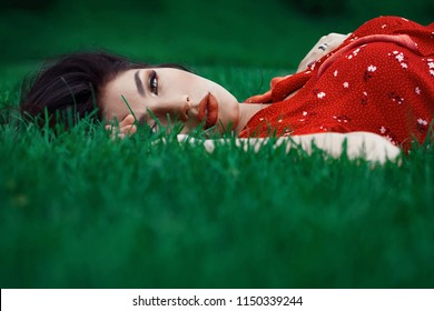 Side view portrait of a beautiful brunette woman in red dress lying green grass. Tanned golden skin, makeup.