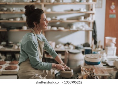 Side view portrait of beautiful craftswoman making clay bowl in pottery workshop. She looking away and smiling