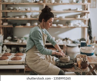 Side view portrait of beautiful craftswoman sitting on bench and shaping clay in pottery workshop