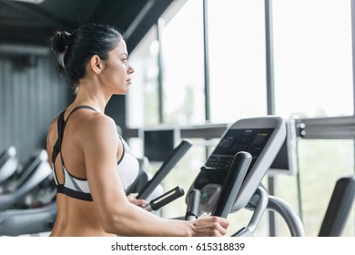 Side view  portrait of beautiful  sportive  woman exercising using elliptical machine   during workout in modern gym against big window