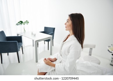 Side view portrait of beautiful woman in white bathrobe sitting on daybed. She is looking away and smiling