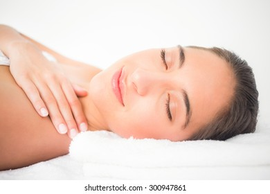 Side view portrait of a beautiful young woman on massage table at spa center