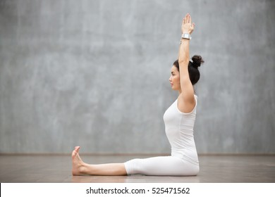 Side view portrait of beautiful young woman working out against grey wall, doing yoga or pilates exercise without mat on wooden floor. Model sitting in Dandasana, Staff pose. Full length