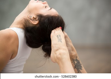 """Side view portrait of beautiful young woman with tattoo on her foot meaning """"Wild kitty"""" working out against grey wall, doing yoga or pilates exercise. King Cobra Pose, Raja bhudjangasana. Close up"""