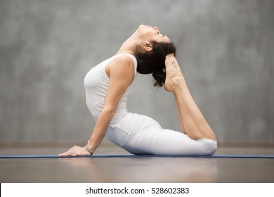 """Side view portrait of beautiful young woman with tattoo on her foot meaning """"Wild kitty"""" working out against grey wall, doing yoga or pilates exercise. King Cobra Pose, Raja bhudjangasana. Full length"""
