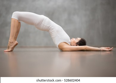 """Side view portrait of beautiful young woman with tattoo on foot meaning """"Wild cat"""" working out in fitness club or at home, doing yoga, pilates exercise. Variation of shoulder bridge pose. Full length"""