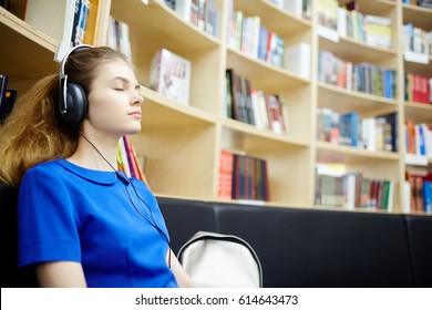 Side view portrait of beautiful young woman listening to audiobook wearing big headphones, closing eyes and relaxing in modern library