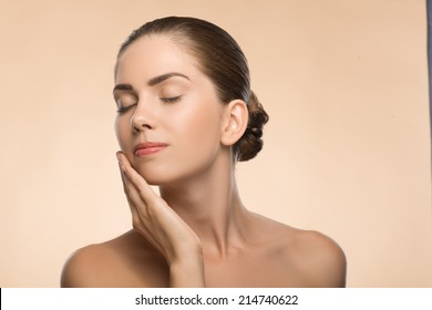 Side view Portrait of beauty face of beautiful girl with clean and  fresh skin closed eyes  touching her face isolated on beige background with copy place