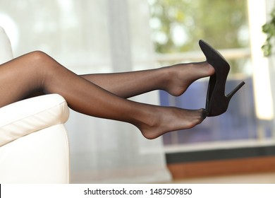 Side view portrait of a beauty woman legs with nylons taking off shoes lying on a couch at home
