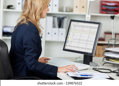 Side view portrait of businesswoman using computer at office desk