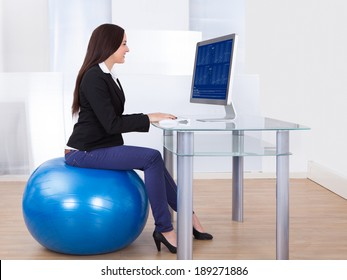 Side view portrait of businesswoman using computer while sitting on pilates ball in office
