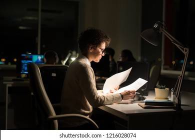Side view portrait of busy businesswoman working late in dark office, copy space