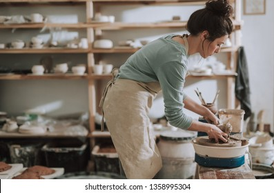 Side view portrait of charming craftswoman kneading and shaping clay on pottery wheel