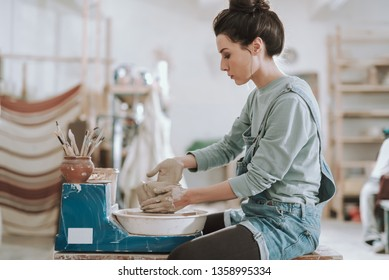 Side view portrait of charming craftswoman in denim overalls making clay pot in pottery workshop