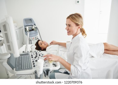 Side view portrait of charming physician in white lab coat looking at monitor of ultrasound machine while young woman lying on daybed and smiling