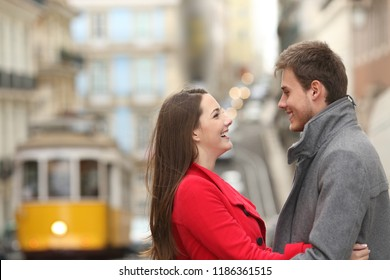 Side view portrait of a cheerful couple looking each other in the street