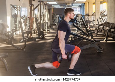 Side view portrait of concentration young adult sport man athlete working out in gym, standing on the knees and holding two dumbbells, doing exercises for legs and squatting. indoor, looking at camera