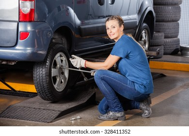 Side view portrait of confident female mechanic fixing car tire with rim wrench at garage