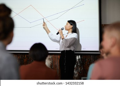 Side view portrait of contemporary businesswoman giving presentation pointing at graph lines on projector screen during lecture, copy space