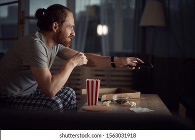 Side view portrait of contemporary man watching TV in dark and eating pop corn while enjoying late night movies, copy space