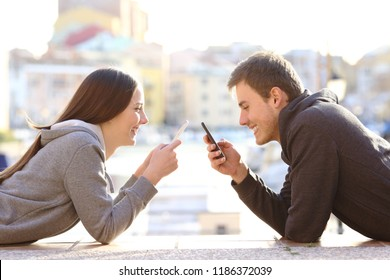 Side view portrait of a couple of teens using their smart phones on vacation