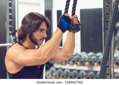 Side view portrait of a determined young man exercising triceps pulldown at cable machine during upper body workout at the gym