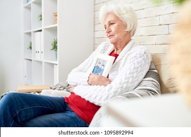 Side view portrait of devastated senior woman lovingly hugging framed photograph of her husband sitting at home alone in armchair by brick wall photo in frame by me .