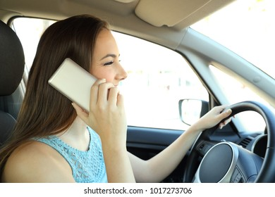 Side view portrait of a distracted driver calling on phone driving a car