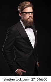 Side view portrait of a elegant business man holding his hands in pockets on black studio background.