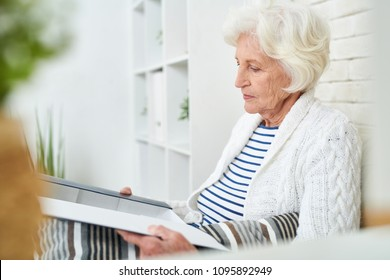 Side view portrait of elegant senior woman opening box of photos and cherished little things remembering her family and friends while sitting alone at home in modern apartment.