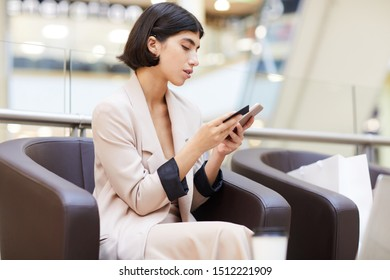 Side view portrait of elegant young woman holding credit card and smartphone while enjoying e-shopping, copy space