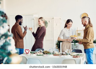 Side view portrait of elegant young people enjoying Christmas party and smiling happily while mingling in dining room, copy space