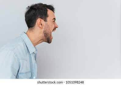 Side view portrait of emotional mad stylish young male screams loudly and with anger, being stressed, expresses negative emotions, isolated over white background. Emotions, feelings and people concept