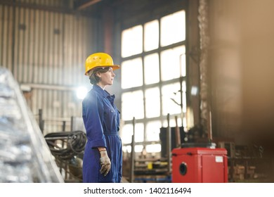 Side view portrait of empowered woman wearing hardhat posing confidently standing in industrial workshop, copy space