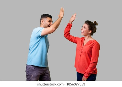 Side view portrait of excited amazed young couple in casual wear standing saying hello and giving high five, friends greeting each other, glad to meet. isolated on gray background, indoor studio shot