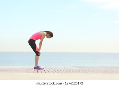 Side view portrait of an exhausted runner resting on the beach after exercise