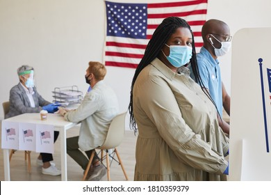 Side view portrait of female African-American voter standing in booth and looking at camera on post-pandemic election day, copy space