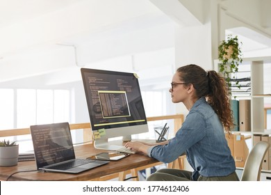 Side view portrait of female IT developer typing on keyboard with black and orange programming code on computer screen and laptop in contemporary office interior, copy space - Shutterstock ID 1774612406