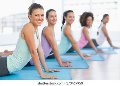 Side view portrait of a fit class doing the cobra pose in a bright fitness studio