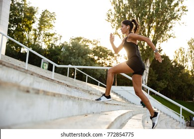 Side view portrait of a fitness woman in earphones running up the stairs outdoors
