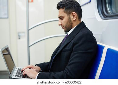 Side view portrait of focused Middle-Eastern businessman working in subway train using laptop