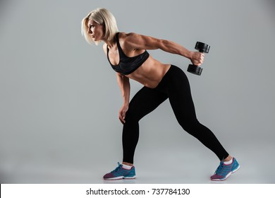 Side view portrait of a focused muscular adult sportswoman working out with a heavy dumbbell and looking away isolated over gray background